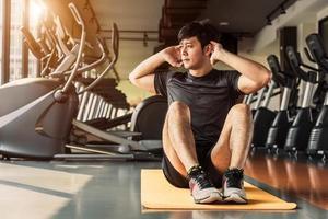 sport man gör crunch eller sitta upp hållning på yogamatta i fitness gym på bostadsrätt med gym utrustning bakgrund. kontor arbetande människor livsstil och sport träning koncept foto