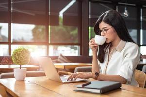 asiatisk arbetskvinna som använder bärbar dator och dricker kaffe på café. människor och livsstil koncept. teknik och affärstema. frilans och yrke tema. arbetsnarkoman i nattkoncept foto