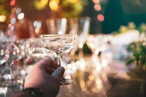 närbild hand som håller martini vinglas på utomhus counter bar i trädgården på natten för fest fest foto