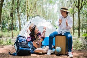 asiatisk tjej och mamma som spelar musik i utomhus skog. människor och livsstil koncept. tema för natur och resor foto