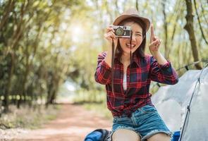 asiatisk skönhetsresenär som tar fotografi av digitala cemera medan han vandrar på camping. äventyrs- och fritidsaktivitetskoncept. lyckligt liv och teknik tema. solo girl tema foto