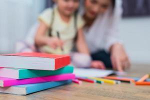 närbild av böcker på golvet med mamma och barn bakgrund. tillbaka till skolan och utbildning koncept. barn och lärartema foto