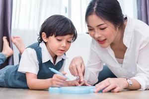 asiatisk mamma som lär söt pojke att rita rött hjärta ombord med färgpenna. tillbaka till skolan och utbildning koncept. familj och hem söt hem tema. tema för förskolebarn. sikt framifrån foto