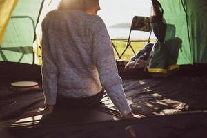 bakifrån av glad kvinnlig turist som kopplar av i campingtält med berg- och solblusbakgrund. människor och livsstil koncept. resor och semester på utomhusäng. turism och vandringstema foto