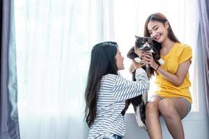 två kvinnor bär och leker med katt. livsstil och människor koncept. lesbiskt tema foto