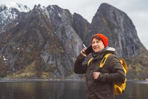 man pratar i mobiltelefon i en gul ryggsäck som står på en bakgrund av ett berg och en sjö foto