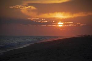 vacker solnedgång på stranden nära havet foto
