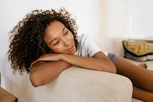 svart ung kvinna leende medan hon vilar på soffan hemma foto