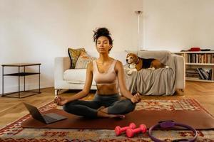 svart ung kvinna mediterar under yogapraksis med sin hund foto