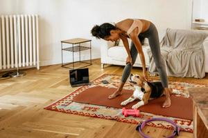 svart ung kvinna leende och stryka hennes hund under yogapraksis foto