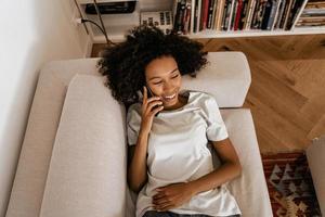 svart ung kvinna som pratar i mobiltelefon medan hon vilar på soffan foto
