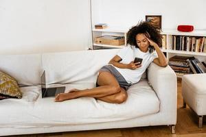 svart ung kvinna som använder mobiltelefon medan hon vilar på soffan foto