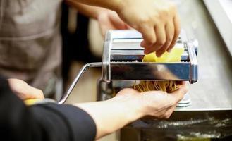 kock som gör pasta med en maskin, hemlagad färsk pasta foto
