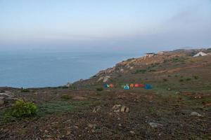 tidig morgon på campingön bildar stenar och solsken ett vackert landskap foto