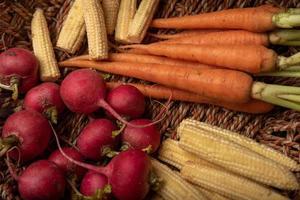 eftermiddagssolen lyser på de röda och orange rädisorna i korgen foto