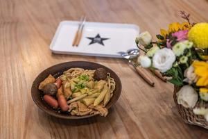 en skål med nudelsoppa med korv, grönsaker och kött ligger på bordet foto