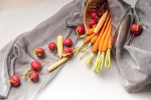 de röda och orange rädisorna finns på den vita duken foto