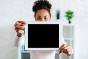flicka som håller en surfplatta med en tom skärm på en suddig bakgrund foto
