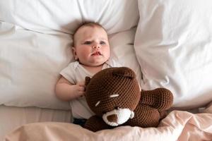 söt, vacker liten flicka som ligger på sängen med en nalle foto
