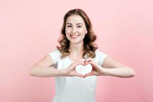 inomhusporträtt av upphetsad lockig kvinna gör en gest ett hjärta med fingrarna. - bild foto