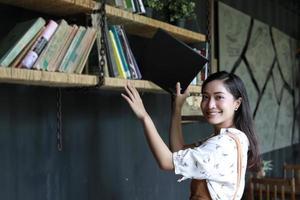 asiatiska kvinnliga studenter håller för avsnitt på bokhylla foto