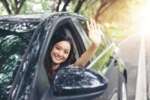vacker asiatisk kvinna leende och njuter. kör bil på väg för resor foto
