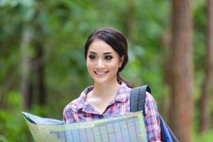 unga kvinnor vandrare tittar på karta och slappna av på semester koncept resor i skogen foto