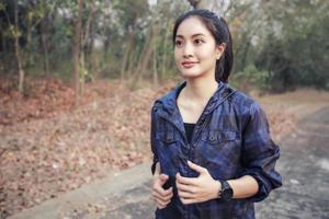 asiatiska kvinnor springer och joggar under utomhus på vägen i parken foto