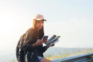 asiatiska unga kvinnor människor vandrar med vänner ryggsäckar går tillsammans och tittar på kartan och tar fotokamera vid vägen och ser lyckliga ut, slappna av på semester konceptresor foto