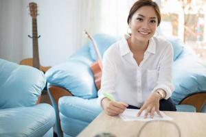 vackra asiatiska affärskvinnor som skriver datakontrolldokument och ler glada över att arbeta foto