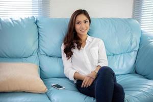 asiatiska kvinnor leende glada för avkoppling på soffan hemma foto