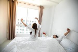 parälskare som vaknar i sin säng helt utvilade och öppnar gardinerna på morgonen för att få frisk luft. foto