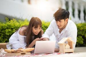 lyckliga romantiska par älskare pratar och dricker vin medan de har en picknick hemma foto