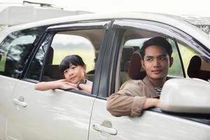 glad liten flicka med asiatisk familj som sitter i bilen för att njuta av roadtrip och sommarlov i husbil foto