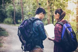 asiatisk grupp ungdomar som vandrar med vänner ryggsäckar går tillsammans och tittar på karta och tar fotokamera vid vägen och ser lyckliga ut, slappna av på semester konceptresor foto