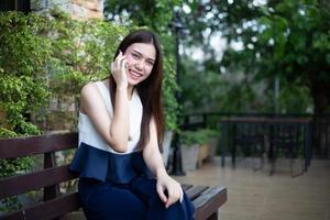 asiatiska affärsmän och kvinnor använder mobiltelefon och touch smartphone för kommunikation och kontroll av affärsmän i kontorsbakgrund foto