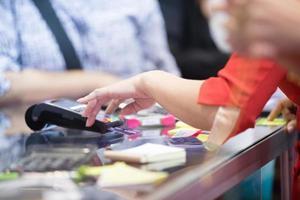 asiatiska affärskvinnor handen använder kreditkortsmaskin för betalning i cafeteria och stormarknad foto