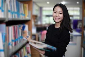 asiatiska kvinnliga studenter håller för urval bok i biblioteket foto