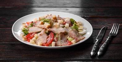 utsökt färsk sallad med bacon och tomater med kryddor och gröna foto