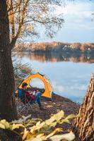 man sitter vid stranden av sjön nära tältet foto