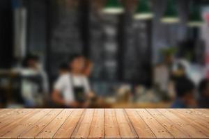 trä bordsskiva med oskärpa av människor i kafé eller café, restaurang bakgrund foto