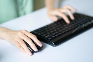 asiatisk kvinna som använder mus och tangentbord för att arbeta foto