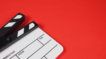 klaffbräda i studioskytte. det används i videoproduktion och filmindustri på röd bakgrund. foto
