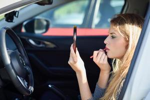 blond kvinna som applicerar läppstift och tittar på spegeln i sin bil foto