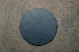 tom pizzafat för hemlagad bakning uppsatt på mörk betong. mat recept koncept på mörk sten bakgrund textur med kopia utrymme. foto
