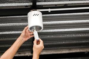 mänsklig hand installerar en led -lampa i en cirkulär taklampa. foto