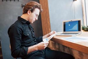 affärsman som använder bärbar dator med surfplatta och penna på träbord i kafé med en kopp kaffe. en entreprenör som hanterar sitt företag på distans som frilansare. foto