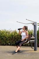 glad kvinna som tränar på idrottsplatsen i solig sommardag, dricker vatten från flaskan foto