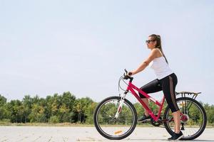 bekymmerslös kvinna som cyklar i en park foto