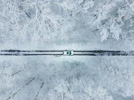 vy över den vita bilen uppifrån i frusen vinterskog foto